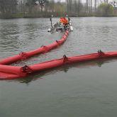Barrage de confinement tracté par un petit bateau